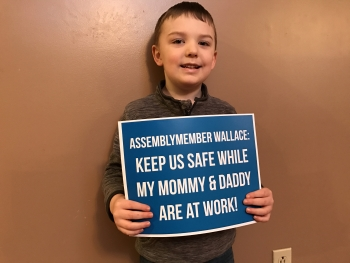 Child holding a sign with a message to Assemblymember Wallace