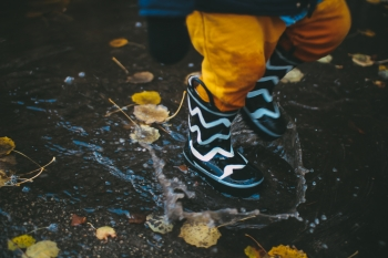 A child with boots running in a puddle