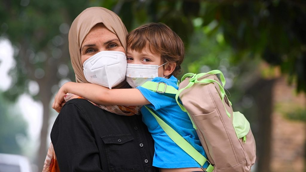 Woman and child wearing masks