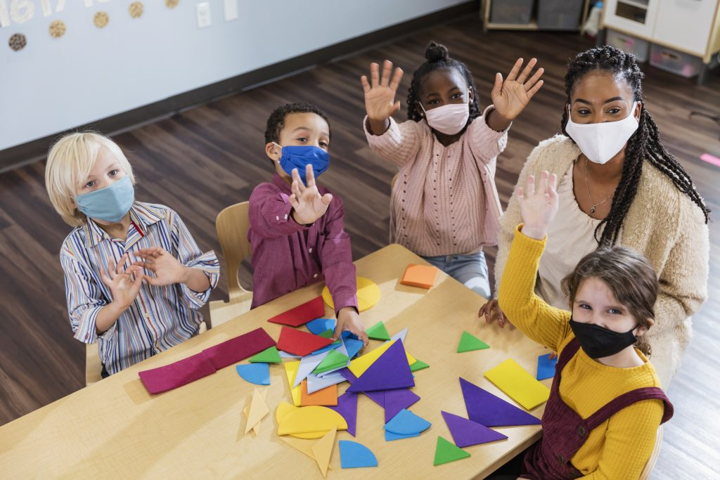 Classroom of toddlers with teacher wearing mask